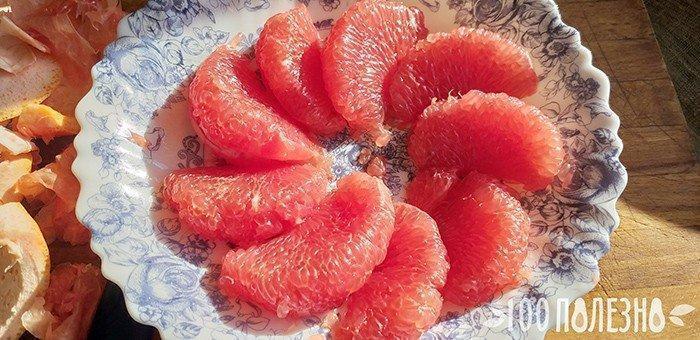 Очищенные дольки грейпфрута на тарелке